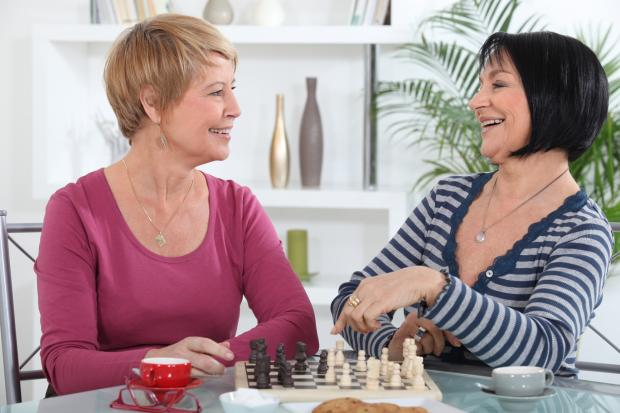 Two female friends playing chess together