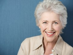: Beautiful elegant elderly lady with a lively smile looking directly at the camera while posing against a green background with copyspace